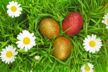 Easter background with grass, flowers and colorful glitter eggs