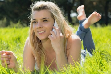 Pretty blonde lying on grass talking on phone