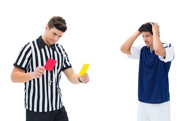 Referee showing yellow card to football player