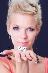 beautiful young woman holding dice as symbol of risk and luck