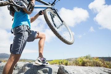 Fit man walking up rocky terrain holding mountain bike