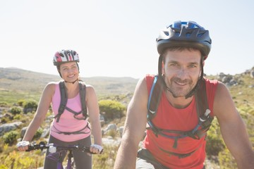 Fit cyclist couple riding together on mountain trail