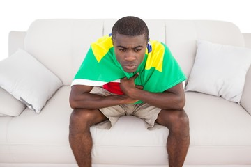 Upset brazilian football fan sitting on couch