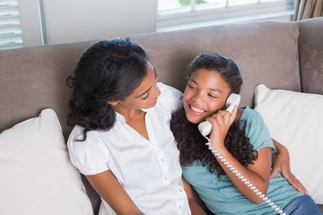 Happy mother and daughter on the phone together on sofa
