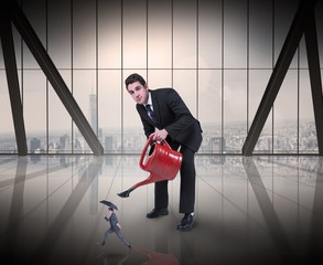 Composite image of businessman watering tiny businessman