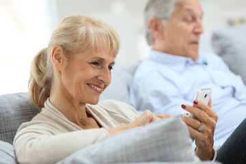 Senior woman using smartphone, husband reading book