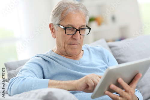 canvas print picture Senior man reading news on digital tablet