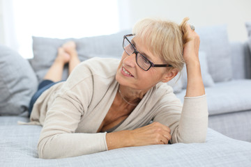 Smiling senior woman with eyeglasses laying on couch