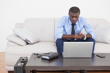 Handsome businessman using laptop on sofa