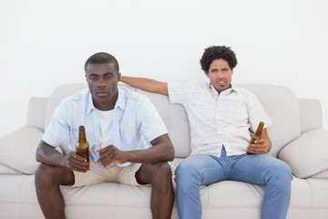 Football fans sitting on couch drinking beer