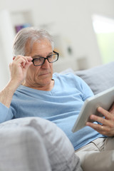 Senior man reading news on digital tablet