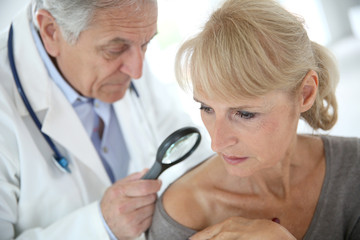 Doctor using magnifying glass to check on beauty spot