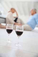 Glasses of wine set on floor, senior couple in background