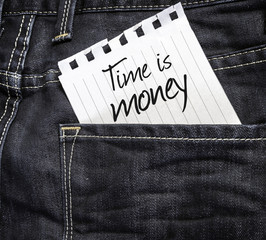 Time is Money written on a peace of paper on a jeans background