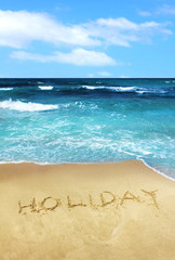Holiday written in beach sand