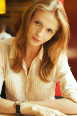 Smiling young beautiful red-haired student girl in cafe