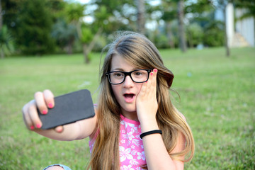 cute teenage girl doing selfie in the park