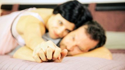Couple in love holding hand in bed