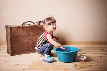 little child plays with toy and water indoor