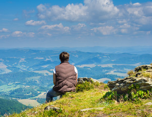 Woman sitting and looking at the Carpathian Mountains
