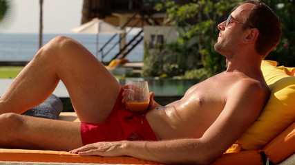 Happy man drinking cocktail on sunbed, lying on sunbed by villa