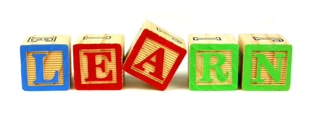 Toy wooden blocks spelling LEARN over a white background
