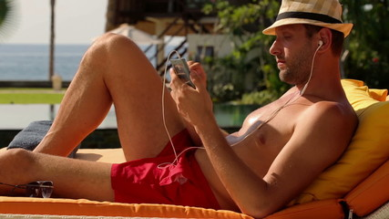 Young man listen to the music on phone, lying on sunbed