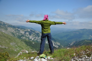 Young woman standing on a cliff with raised hands