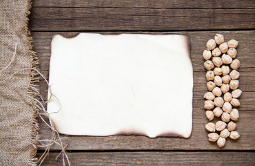 Card, chickpea, burlap and dark wood background