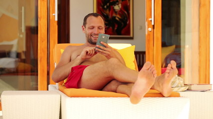 Young man on sunbed taking selfie photo with smartphone