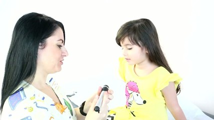 Female Pediatrician performing an eye exam on a female child