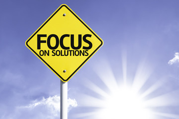 Focus on Solutions road sign with sun background