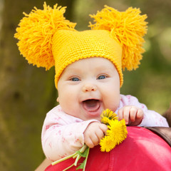 baby in yellow knitted cap with dandelions
