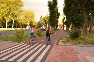 dos chicas circulando en bicicleta por la ciudad