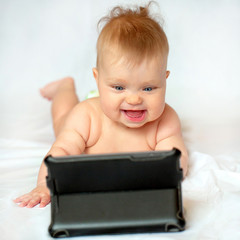 Smiling baby with tablet pc at home