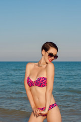 Young beautiful girl in swimsuit and sunglasses at the beach