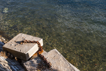 Concrete blocks and marine chain by the water