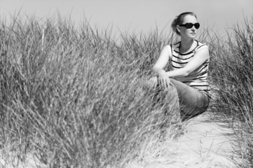 Woman in sand dunes amongst tall grass enjoying sunny day