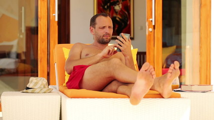 Man with smartphone relaxing on sunbed by luxury villa