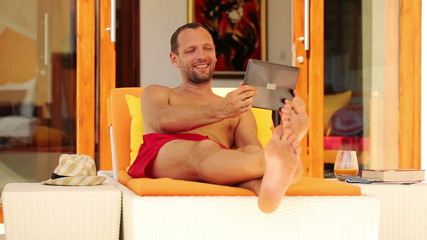 Man chatting on tablet while lying on sunbed by luxury villa