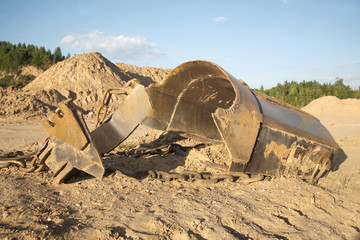 Broken big heavy bucket lies on sand on summer day