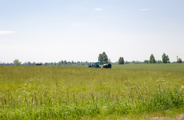 working tractor with water tank in pasture meadow
