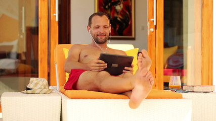 Young man watching movie on tablet computer, lying on sunbed