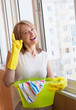 Happy woman washes window in the new apartment