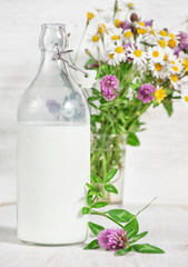 Fresh milk in old fashioned bottle and wildflowers