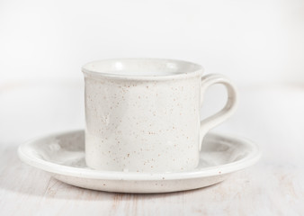 Ceramic mug with milk and saucer