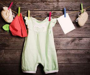 children's clothing and paper on a wooden background