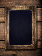 Aged  menu blackboard over vintage wooden background. Empty Chal