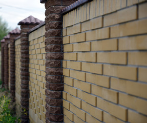 Fence of yellow and brown bricks