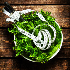 Salad with fitness  measuring tape over wooden background